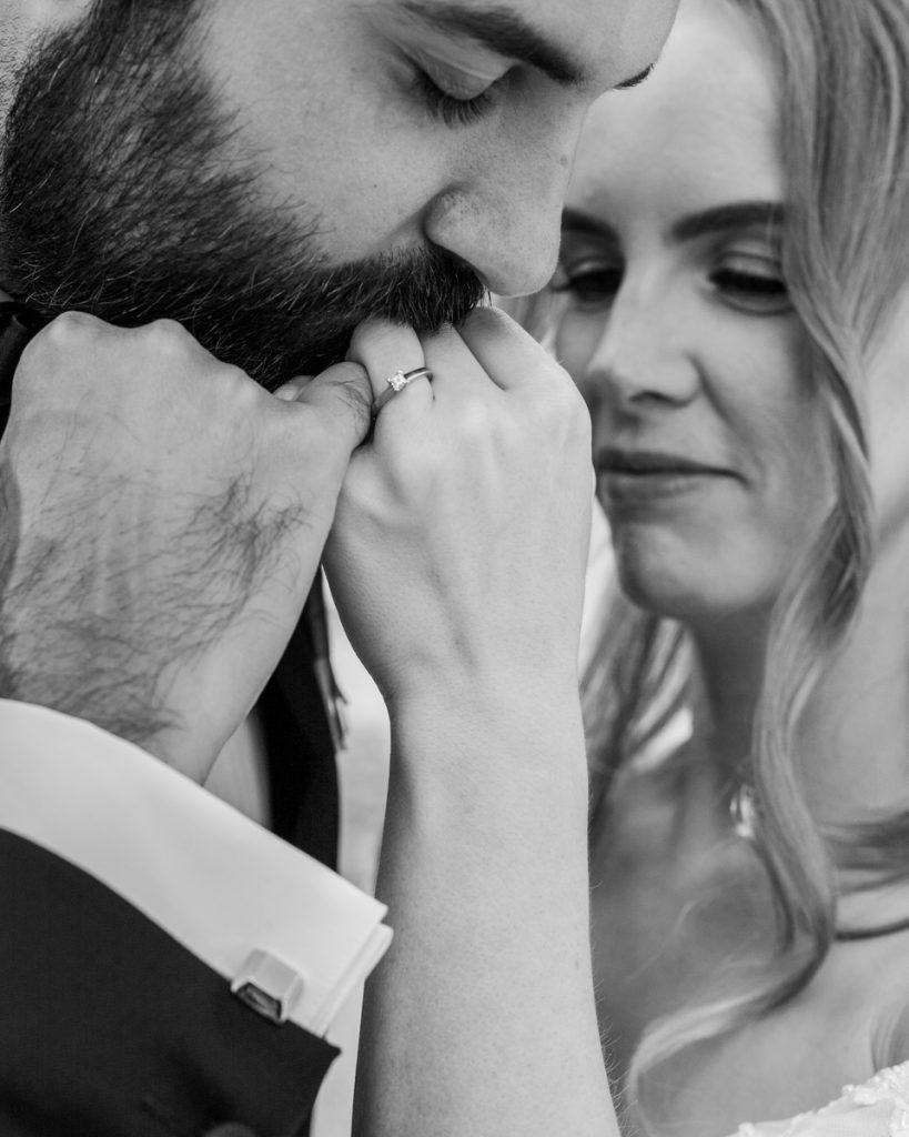 elopement wedding as groom is kissing his brides ring finger