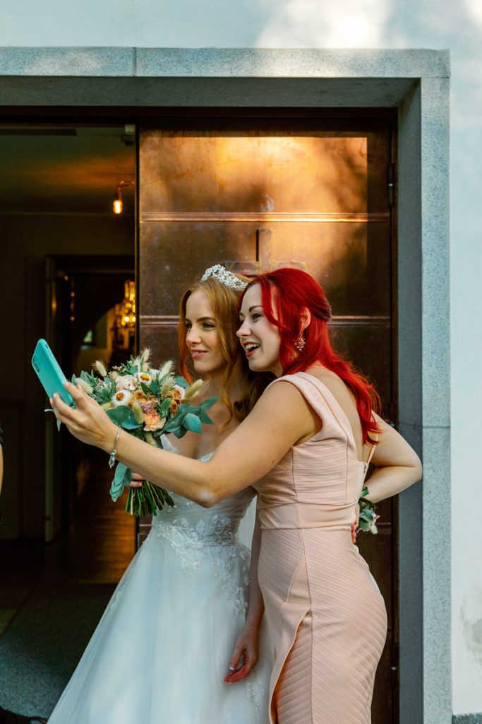 elopement wedding bride and bridesmaid taking a selfie outside of Bromma church