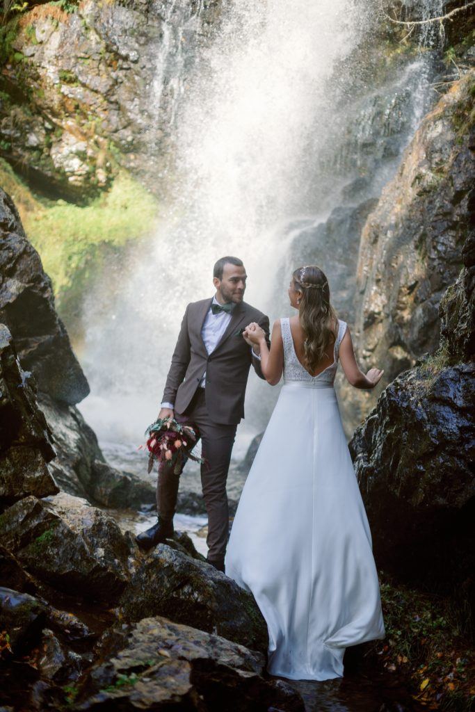 mountain waterfall elopement couple standing on stones by the waterfall