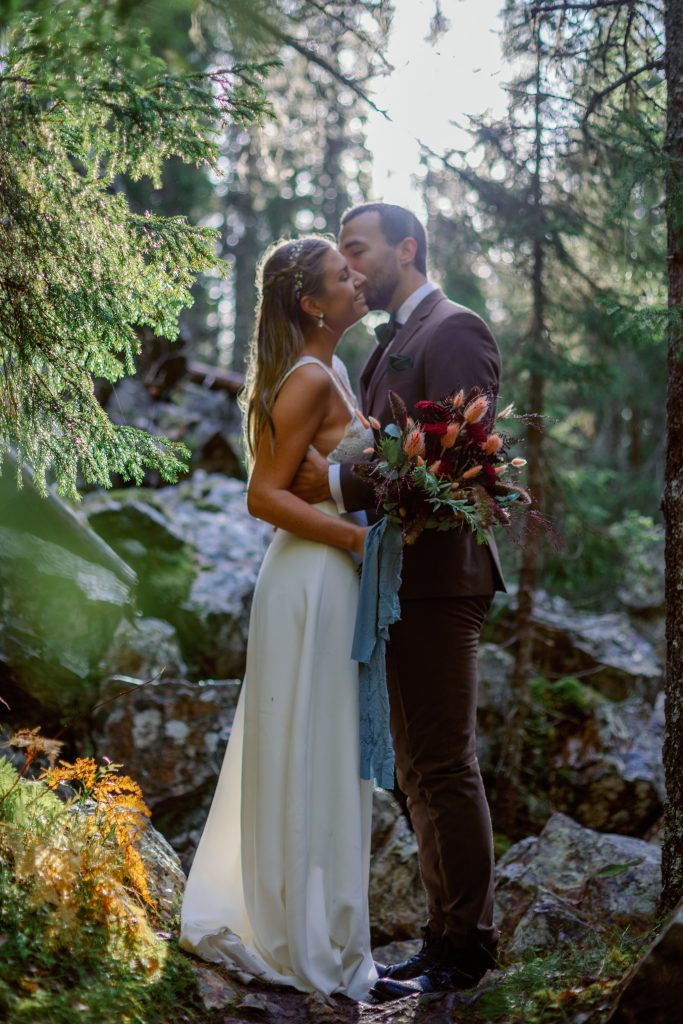 mountain waterfall elopement couple cuddling in mist from the waterfall