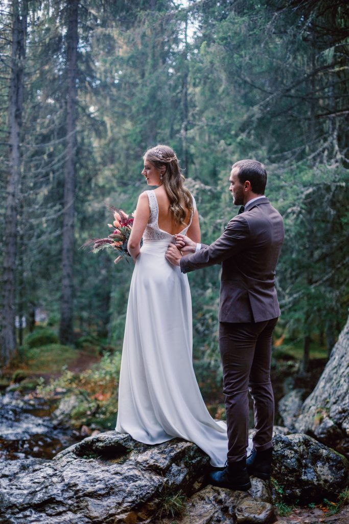 mountain waterfall elopement couple getting ready in front of the waterfall,