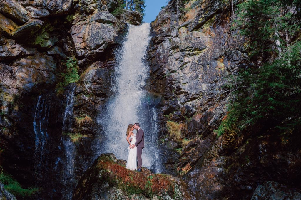 mountain waterfall elopement couple standing on a stone in front of the waterfall, cuddling