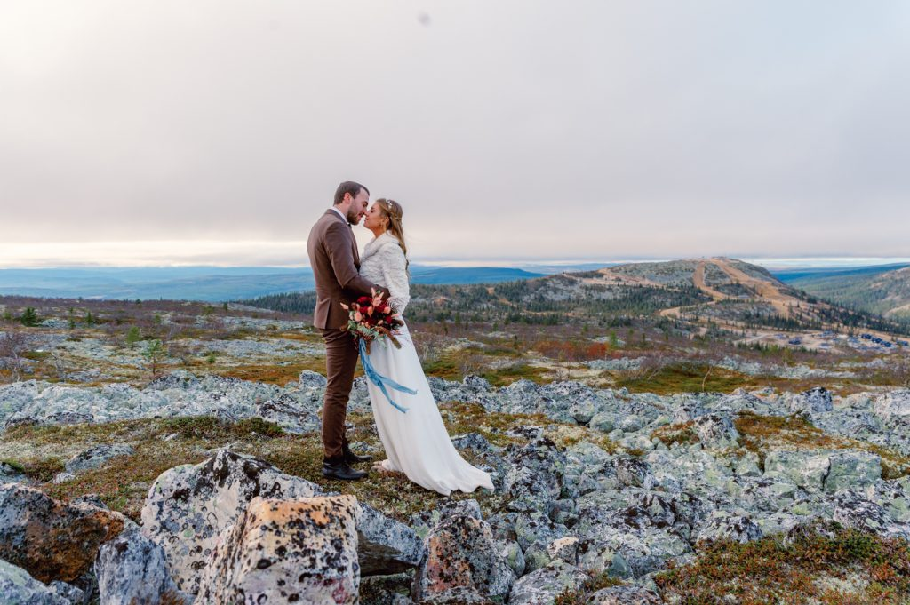 mountain waterfall elopement on a mountaintop when the wind is catching the brides dress