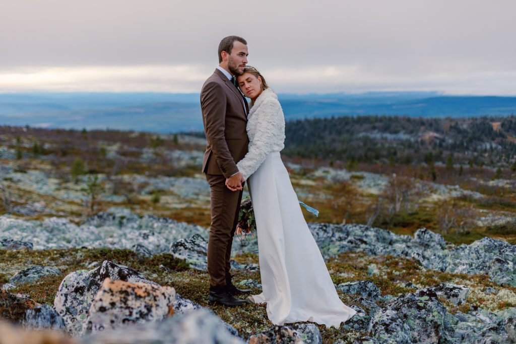 mountain waterfall elopement bride leaning on grooms chest on windy mountain top