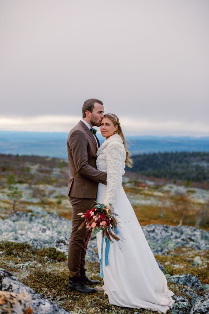 mountain waterfall elopement couple cuddling in mist on a mountaintop