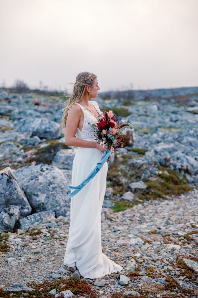 mountain waterfall elopement bride standing in the windy mountain top holding her bouquet