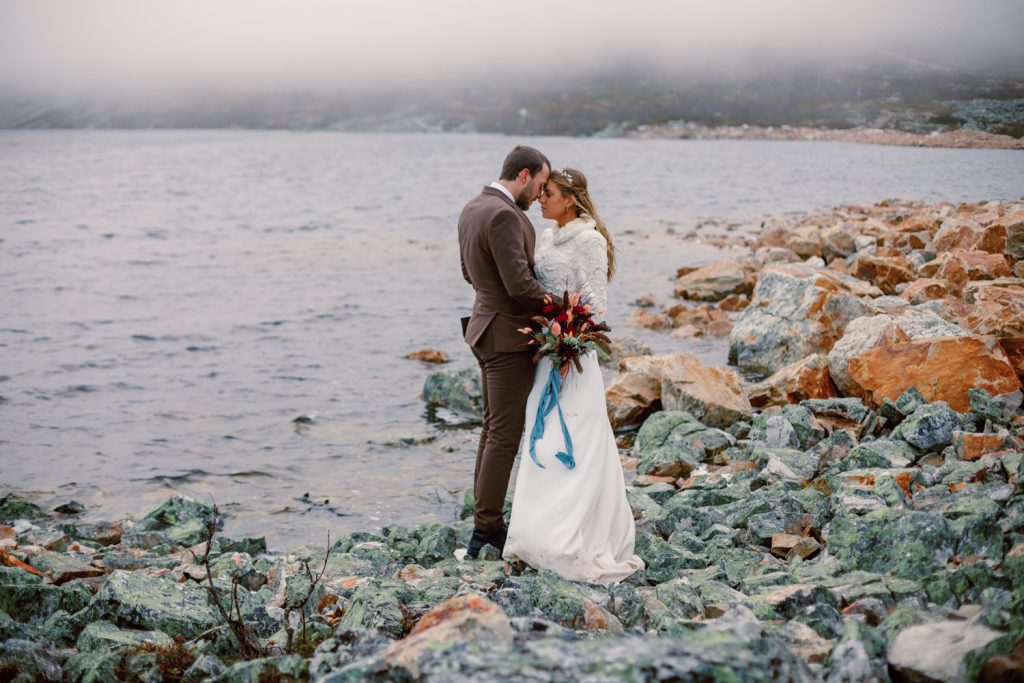 mountain waterfall elopement couple by a mountain lake keeping warm in the wind and mist