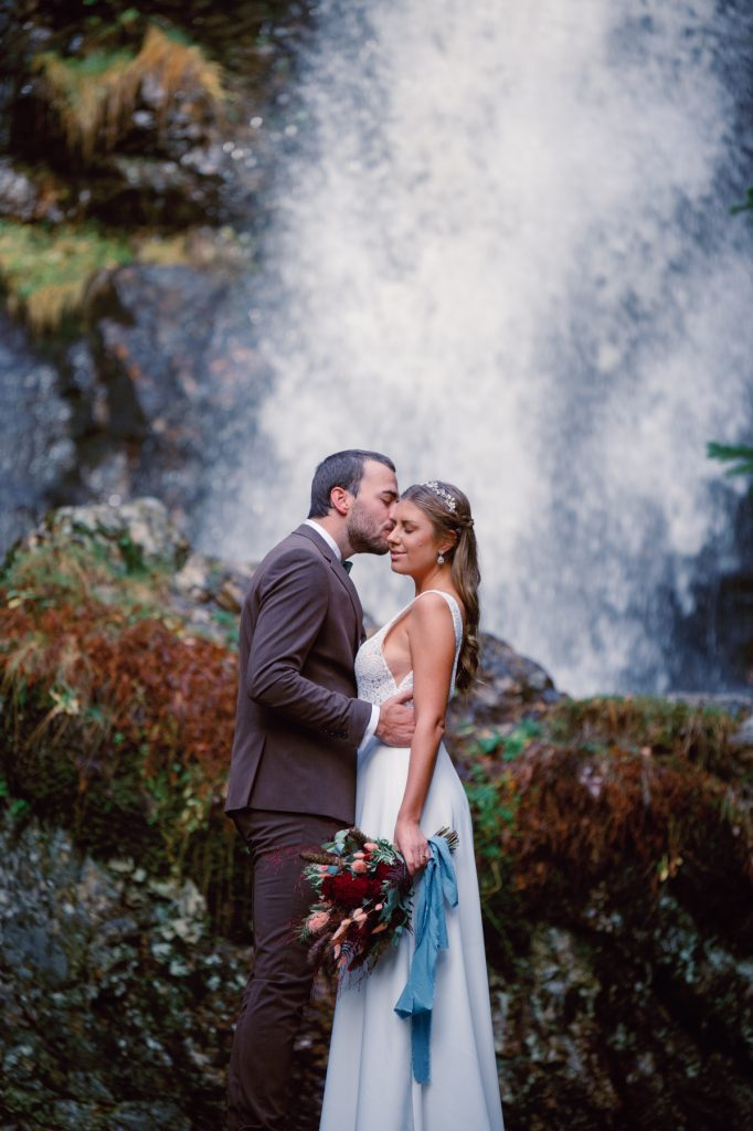 mountain waterfall elopement couple standing in front of a stone in front of the waterfall, cuddling