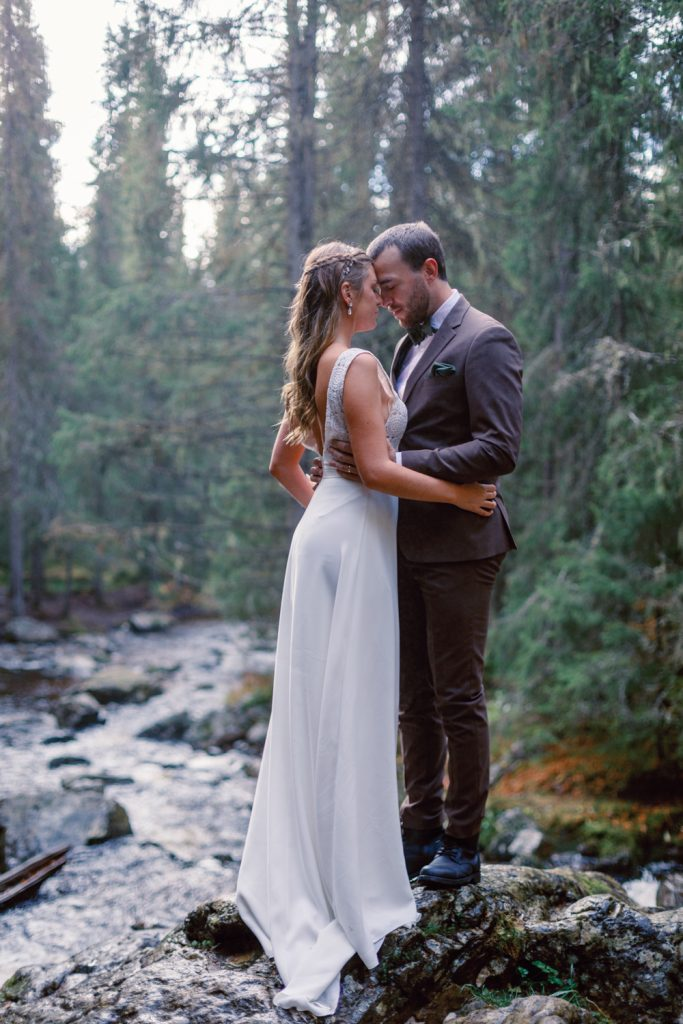 mountain waterfall elopement couple standing by the roaring river by te waterfall